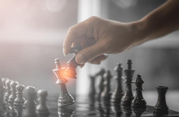 Strategia konkurencji biznesowej i koncepcja sukcesu biznesu. ręka biznesmena poruszający królewiątko c