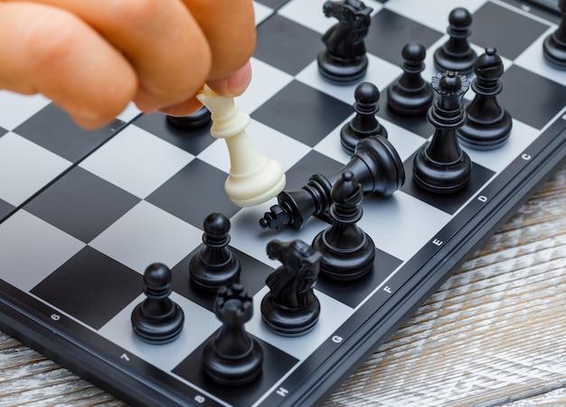 Strategii biznesowej pojęcie na drewnianej tło ręce rusza się szachową postać w rywalizaci.