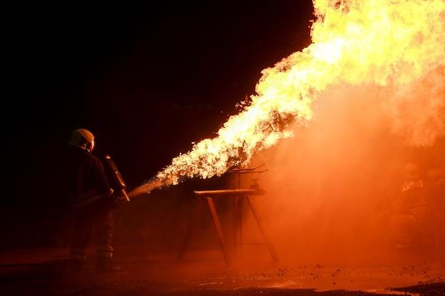 Strażacy noszą odzież przeciwpożarową, aby rozpylać ogień ze zbiorników podczas nocnych ćwiczeń przeciwpożarowych.