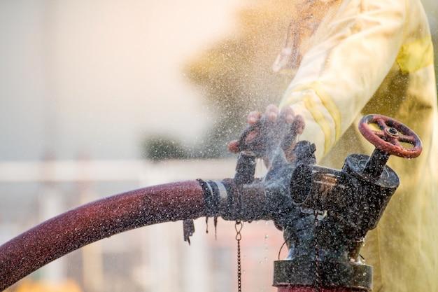 Strażacy używający wody z węża do gaszenia pożaru na szkoleniu przeciwpożarowym grupy ubezpieczeniowej. strażak w kombinezonie przeciwpożarowym dla bezpieczeństwa pod walizką treningową z niebezpieczeństwem.