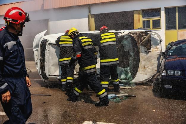 Strażacy w akcji. strażacy gaszący pożar i próbujący przewrócić rozbity samochód w wypadku samochodowym.