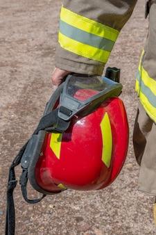Strażak posiadający czerwony kask. zdjęcie pionowe