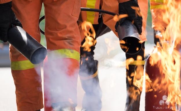 Strażak próbuje zatrzymać ogień przez gaśnicę w szkoleniu przeciwpożarowym.