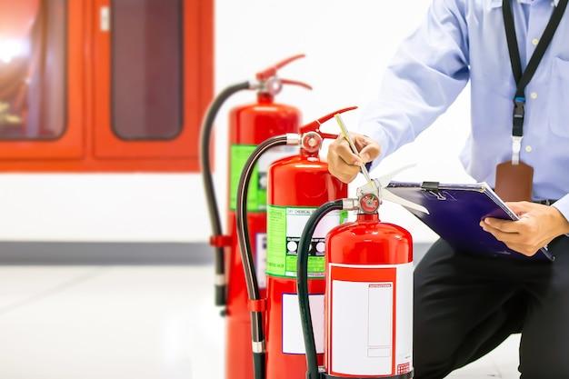 Strażak sprawdzający poziom manometru gaśnicy.