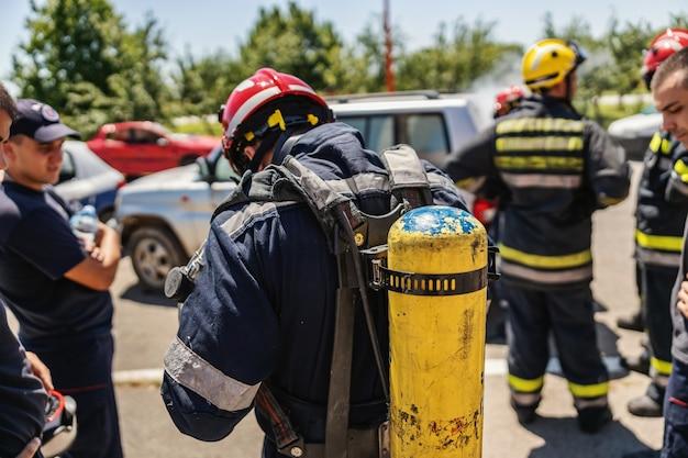 Strażak stojący w grupie innych strażaków z gaśnicą na plecach. przygotowuje się do działania.