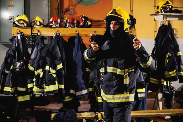 Strażak stojący w remizie, zakładający hełm i przygotowujący się do akcji.