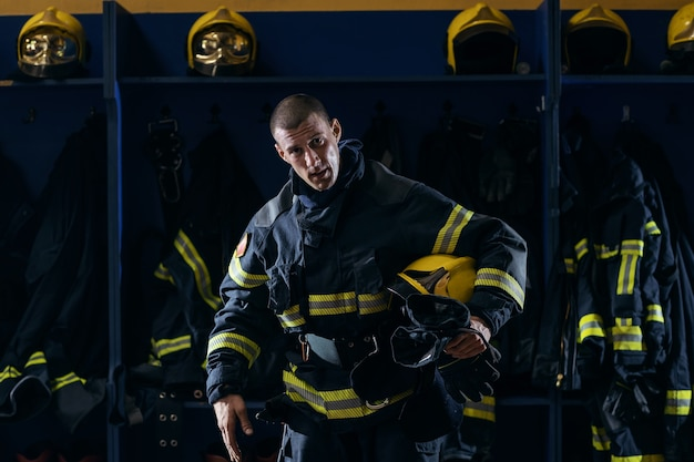 Strażak trzymający hełm pod pachą po akcji, stojąc w remizie.