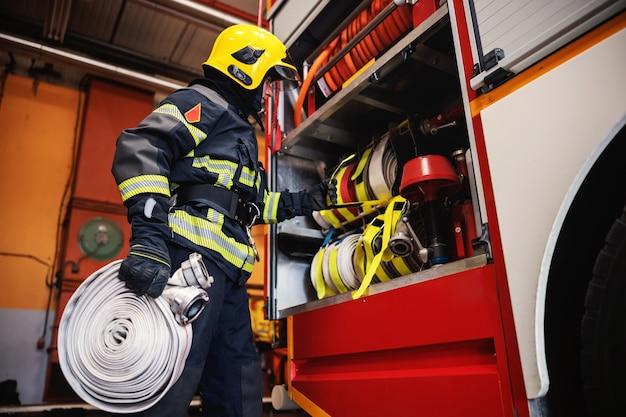 Strażak w mundurze ochronnym z hełmem na głowie sprawdza stan węży przed interwencją, stojąc w remizie.