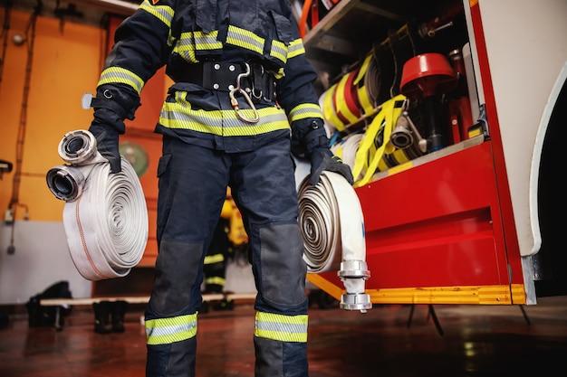 Strażak w mundurze ochronnym z hełmem na głowie sprawdza stan węży przed interwencją w remizie.