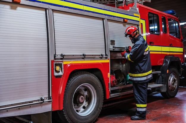 Strażak w mundurze ochronnym z hełmem sprawdzający stan węża w wozie strażackim stojąc w straży pożarnej.