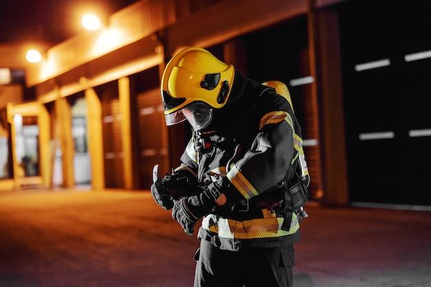 Strażak w mundurze ochronnym z pełnym wyposażeniem przygotowujący się do ugaszenia dużego pożaru.
