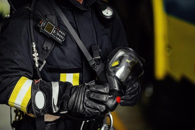 Strażak w mundurze z maską gazową i hełmem w pobliżu wozu strażackiego