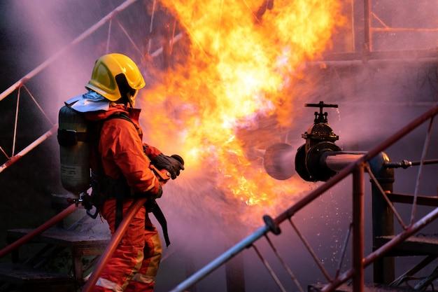 Strażak w nocy rozpylający płomień z rurociągu