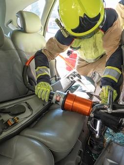 Strażak w wypadku przecina siedzenie narzędziem hydraulicznym