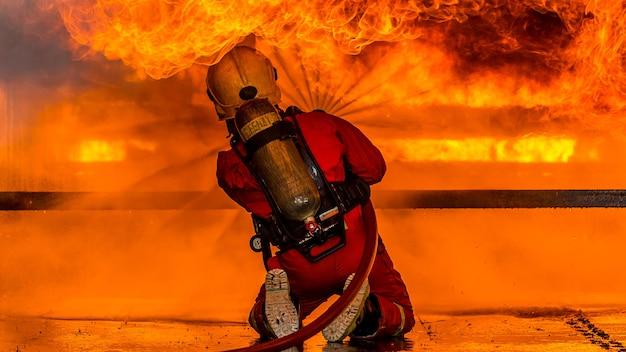 Strażak za pomocą gaśnicy i wody z węża do walki z ogniem