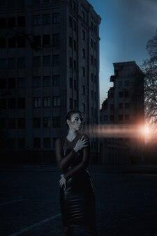 Strażnik o zachodzie słońca w pobliżu zniszczonego budynku. dramatyczny obraz.