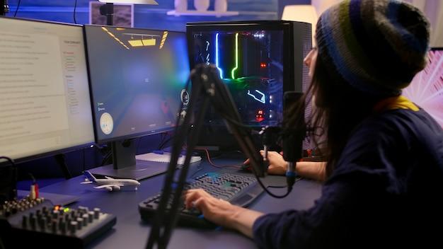 Streamer siedzący na fotelu do gier i grający w strzelankę z perspektywy pierwszej osoby podczas rywalizacji online