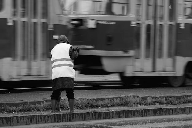 Street cleaner kobieta pracuje wcześnie rano. kobieta robotnik zamiatać ulicę w pobliżu szyn tramwajowych.