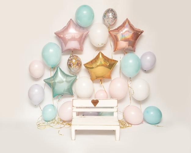 Strefa fotograficzna na białym tle z kolorowymi balonami żelowymi i drewnianą ławeczką z serduszkiem do robienia zdjęć maluchom, strefa części urodzinowej