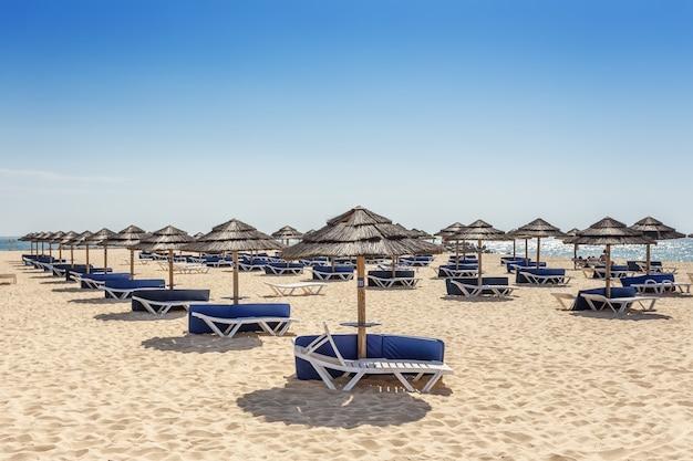 Strefa plażowa do opalania z parasolami i leżakami. portugalia.