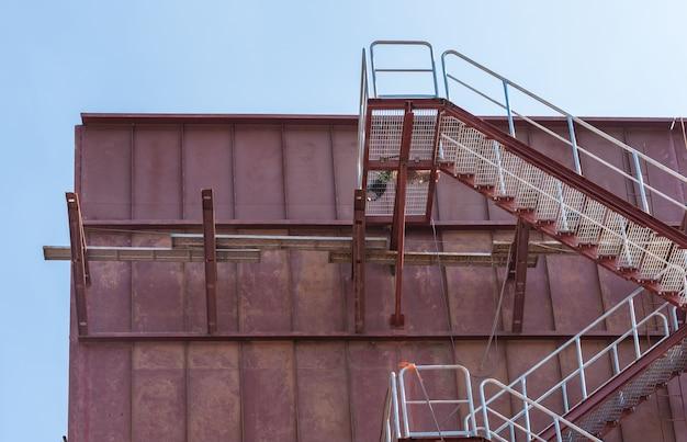 Strefa przemysłowa stali schodowej, konstrukcji i niebieskiego nieba.