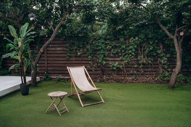 Strefa wypoczynkowa. drewniany fotel i stół na trawniku w ogrodzie. odpoczynek miejsce relaksu. koncepcja odpoczynku