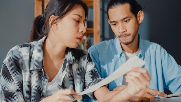 Stres azjatycka para mężczyzna i kobieta używają kalkulatora do obliczania budżetu rodzinnego