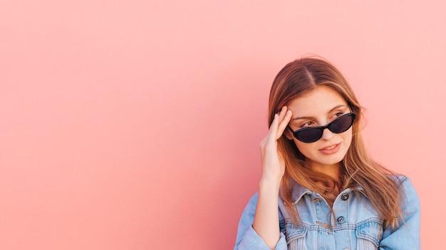 Stres młoda kobieta jest ubranym okulary przeciwsłonecznych patrzeje daleko od przeciw brzoskwinia koloru tłu