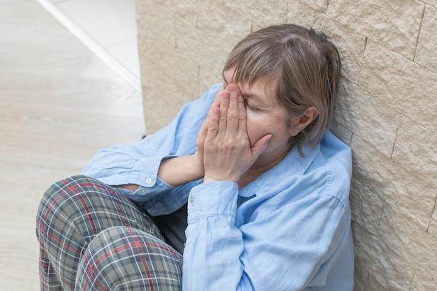 Stres starszy kobieta siedzi na podłodze z twarzą w dłoniach.