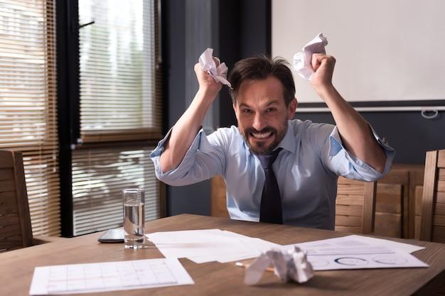 Stres w miejscu pracy. zły, wściekły histeryczny mężczyzna zgniata papier i krzywi się, będąc w pracy