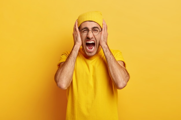 Stresowany, przygnębiony mężczyzna krzyczy głośno, zakrywa uszy, ma dość kłopotów