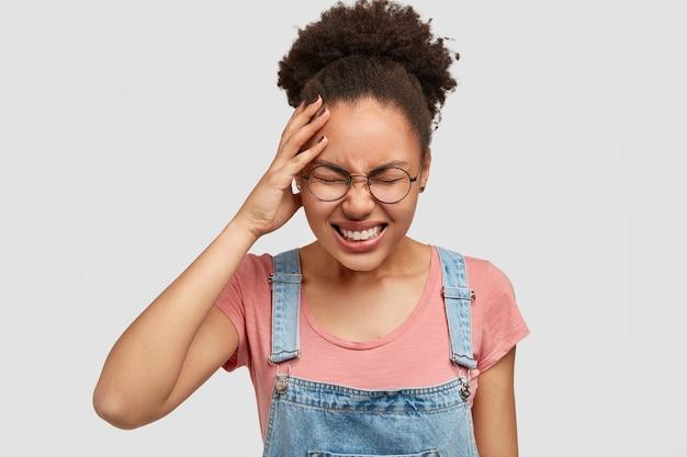 Stresująca ciemnoskóra kobieta cierpi na bóle głowy, ma duże kłopoty, nosi swobodny t-shirt i dżinsowy kombinezon, odizolowany od białej ściany. piękna młoda, przygnębiona african american kobieta