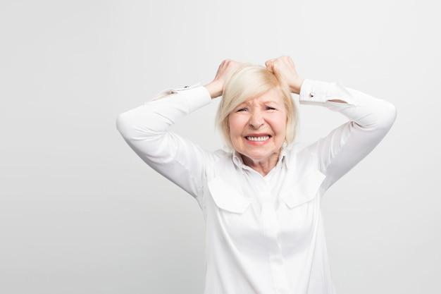 Stresująca i stara kobieta trzyma ręce na rękach i wykazuje pewne depresyjne emocje. ona jest zrozpaczona.