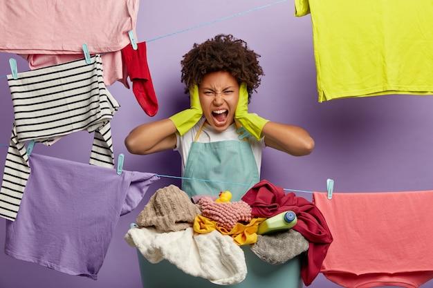 Stresująca młoda kobieta z afro pozowanie z praniem w kombinezonie