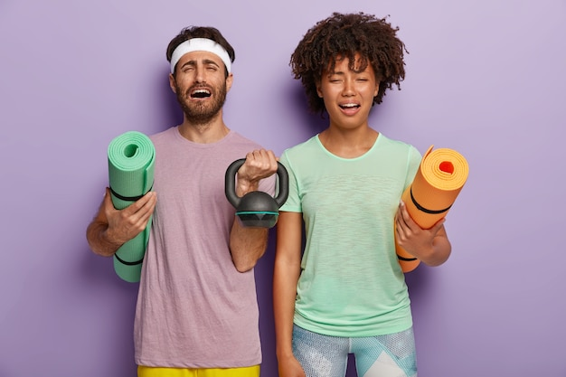 Stresująca różnorodna para czuje się zmęczona po treningu sportowym z trenerem, trzymaniem mat fitness, obciążeniem
