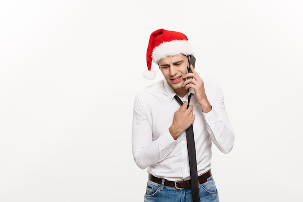 Stresujący biznesmen przystojny poważny rozmawia przez telefon w boże narodzenie.