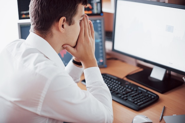 Stresujący dzień w biurze. młody biznesmen trzymając się za ręce na twarzy siedząc przy biurku w biurze twórczym. giełda obrotu forex finanse graficzny koncepcja.