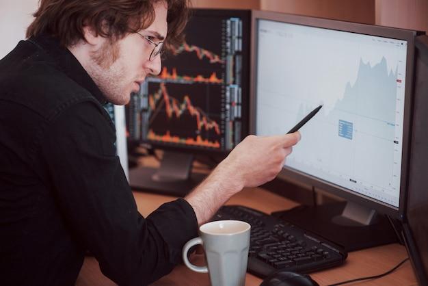 Stresujący dzień w biurze. młody biznesmena mienia ręki na jego twarzy podczas gdy siedzący przy biurkiem w kreatywnie biurze. giełda papierów wartościowych handlu walutami finanse graficzny pojęcie