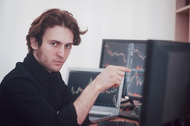 Stresujący dzień w biurze. młody biznesmena mienia ręki na jego twarzy podczas gdy siedzący przy biurkiem w kreatywnie biurze. giełda papierów wartościowych trading forex finanse graficzny pojęcie