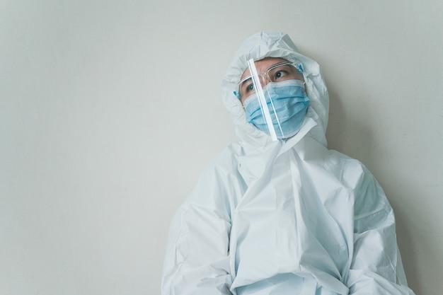 Stresujący - zmartwiony azjatycki personel medyczny siedzący na krześle pod ścianą, pracownik służby zdrowia ciężko pracujący w szpitalu. zapracowany pracownik służby zdrowia - pielęgniarka czuje się zmęczona.
