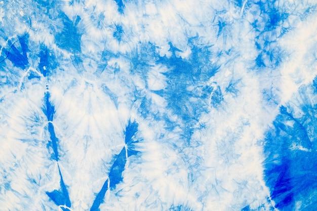 Streszczenie białej tkaniny barwionej niebieskim atramentem indygo, aby stać się szmatką batiku