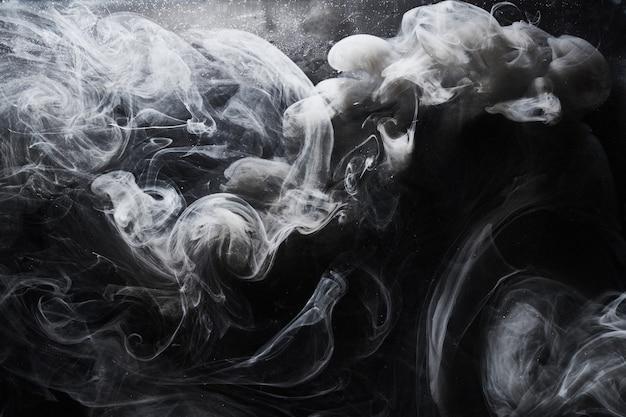 Streszczenie ciemna farba w tle wody. ruch białej chmury dymu na czarnych, akrylowych rozpryskach wirowych