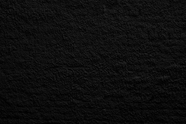 Streszczenie czarne tło. szorstkie nierówności w tynku. powierzchnia ściany.