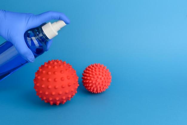 Streszczenie dezynfekcji koronawirusa. walka z wirusem za pomocą środka antyseptycznego. dłoń w gumowej rękawicy medycznej dezynfekuje dwie cząsteczki koronawirusa środkiem antyseptycznym. niebieska rękawica chirurgiczna. skopiuj miejsce