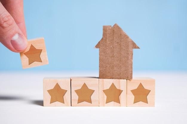 Streszczenie dom z tektury. ręka stawia sześcian z gwiazdą na niebiesko. najwyższa ocena. wycena mieszkań.