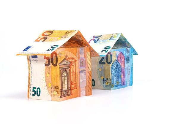 Streszczenie domy z banknotów 50 i 20 euro na białym tle na jasnej powierzchni, koncepcja kredytu mieszkaniowego