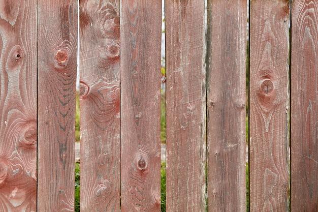 Streszczenie drewniana tekstura w postaci starego wyblakłego płotu z wyblakłą czerwoną farbą i pęknięciami łez.