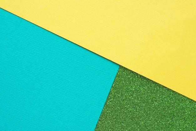 Streszczenie geometryczne zielone świecące tło, niebieski tekstury i żółty papier.