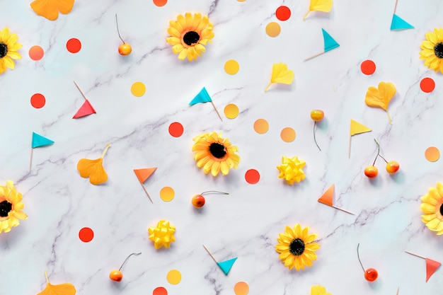 Streszczenie jesień sezonowe tło z żółte kwiaty, liście miłorzębu jesiennego, papierowe konfetti i flagi wykałaczki.