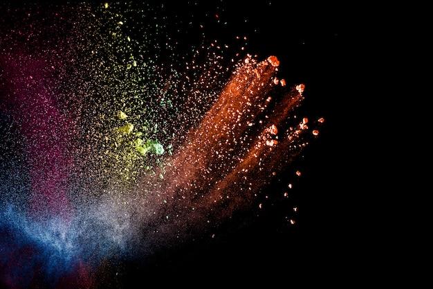 Streszczenie kolorowe cząsteczki pyłu teksturowanej tło. wielobarwny wybuch proszku na czarnym tle.